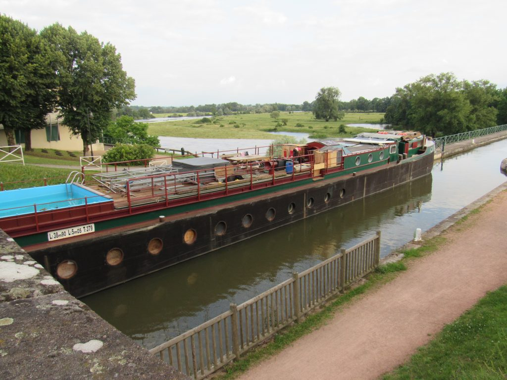 A barge going along the aqueduct over the river Loire